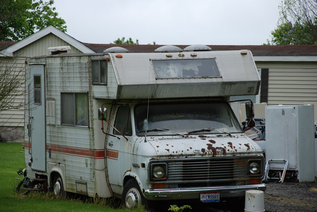 Old and beat up Motorhome parked in a yard