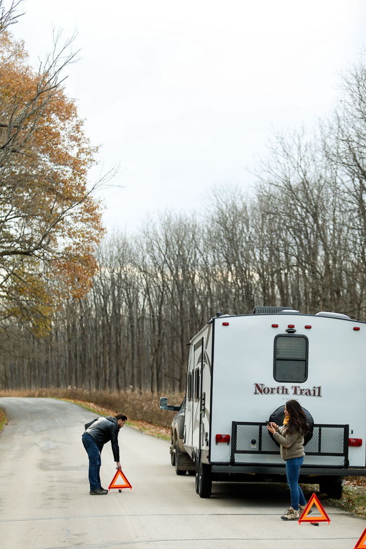 Travel trailer broken down on the side of a road with two people outside placing safety triangles around camper