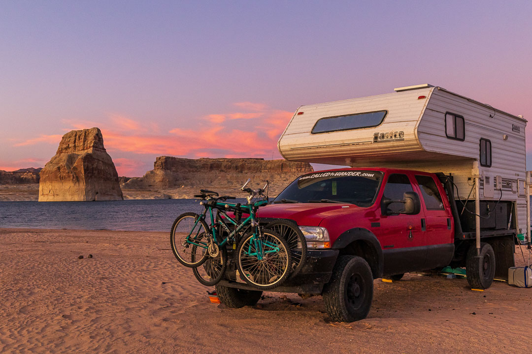 Truck camper boondocking on a lake beach at sunset